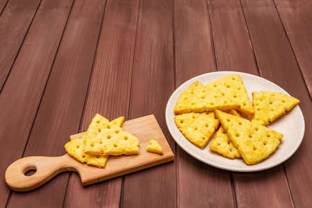 Cheese crackers, salty snack concept. Cookies, plate, cutting board. Wooden planks background, copy space