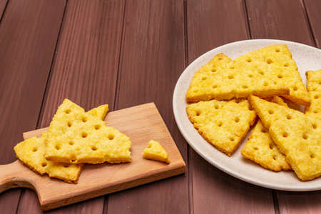 Cheese crackers, salty snack concept. Cookies, plate, cutting board. Wooden planks background, copy space, close up 版權商用圖片