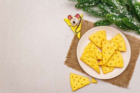 Festive cheese crackers, New Year snack concept. Cookies, mouse figure, fir tree branch, artificial snow, sackcloth napkin. Stone concrete background, copy space, top view