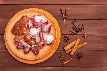 Fresh raw duck offal: heart, liver, stomach. Dry spices: cinnamon, star anise, clove, chili pepper. Wooden boards background, copy space, top view