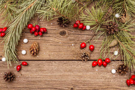 Spirit Christmas background. Fresh dog-rose berries, candies, pine branches and cones, artificial snow. Nature decorations, vintage wooden boards, flat lay, copy space, top view