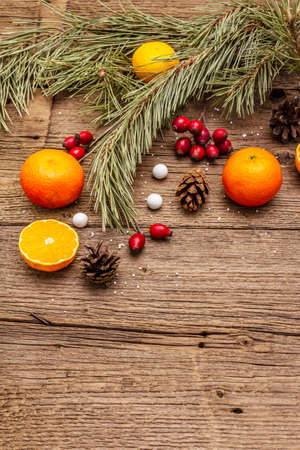 Spirit Christmas background. Fresh mandarins, dog-rose berries, candies, pine branches and cones, artificial snow. Nature decorations, vintage wooden boards, flat lay, copy space