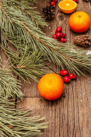 Spirit Christmas background. Fresh mandarins, dog-rose berries, candies, pine branches and cones, artificial snow. Nature decorations, vintage wooden boards, flat lay, copy space, close up Banque d'images