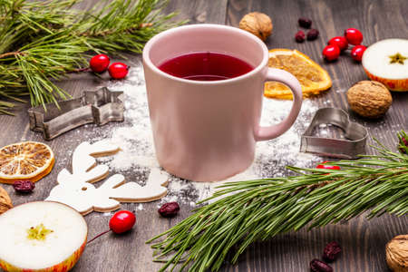 Christmas hot tea background. New Year mood, evergreen pine, nuts, berries, apples, orange. Cookie cutters, flour, deer. Wooden boards, close up