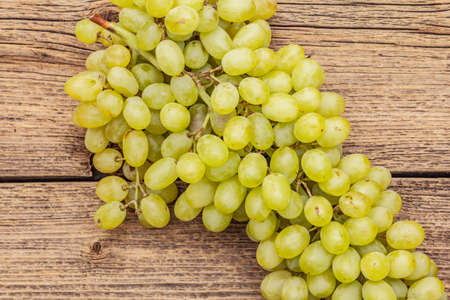 """Bunch of sweet green seedless grapes variety """"Kishmish"""". Ripe fruits autumn harvest. Healthy food concept. Old wooden boards background, top view, close up, macro"""