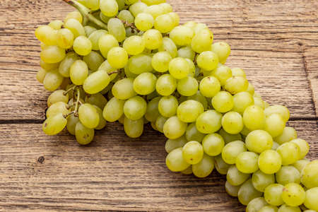 """Bunch of sweet green seedless grapes variety """"Kishmish"""". Ripe fruits autumn harvest. Healthy food concept. Old wooden boards background, close up, macro"""