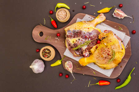 Raw duck legs. Fresh BIO ingredient for preparation traditional French confit. Spice, vegetable, herbs. Animal proteins and healthy fats, wooden board, stone background copy space top view Stock fotó