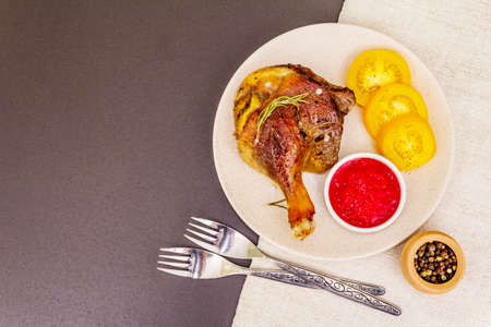 Crusty roasted duck leg. Traditional French food confit preparation. Served with cranberry sauce, fresh tomatoes, dry rosemary. Animal proteins, healthy fats. Stone background copy space top view