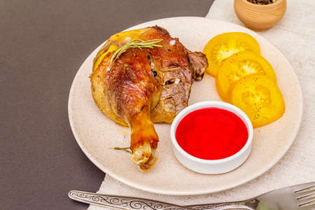 Crusty roasted duck leg. Traditional French food confit preparation. Served with cranberry sauce, fresh tomatoes, dry rosemary. Animal proteins, healthy fats. Stone background close up Stock fotó