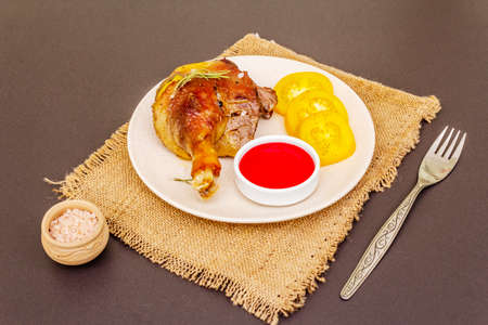 Crusty roasted duck leg. Traditional French food confit preparation. Served with cranberry sauce, fresh tomatoes, dry rosemary. Animal proteins, healthy fats. Stone background copy space Stock fotó