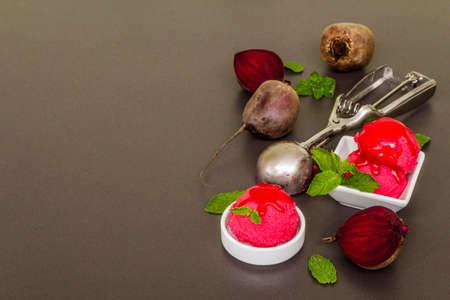 Beet ice cream, sorbet, gelato, sweet icing. Summer healthy refreshment dessert. Vegetarian (vegan) trendy food concept. With fresh vegetables and mint. Stone concrete background, copy space Zdjęcie Seryjne