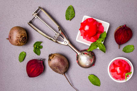 Beet ice cream, sorbet, gelato, sweet icing. Summer healthy refreshment dessert. Vegetarian (vegan) trendy food concept. With fresh vegetables and mint. Stone concrete background, top view