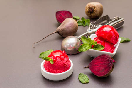 Beet ice cream, sorbet, gelato, sweet icing. Summer healthy refreshment dessert. Vegetarian (vegan) trendy food concept. With fresh vegetables and mint. Stone concrete background, copy space