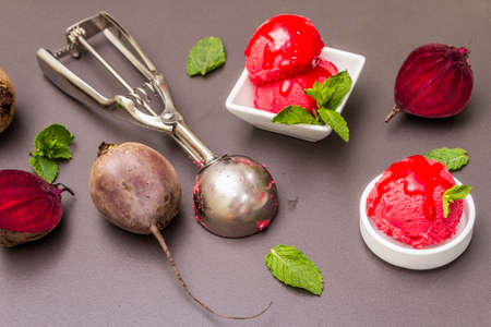 Beet ice cream, sorbet, gelato, sweet icing. Summer healthy refreshment dessert. Vegetarian (vegan) trendy food concept. With fresh vegetables and mint. Stone concrete background Zdjęcie Seryjne