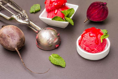 Beet ice cream, sorbet, gelato, sweet icing. Summer healthy refreshment dessert. Vegetarian (vegan) trendy food concept. With fresh vegetables and mint. Stone concrete background, close up