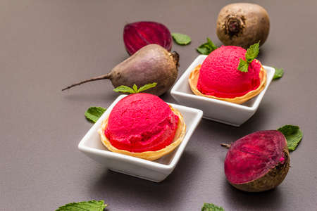 Beet ice cream, sorbet, gelato. Summer healthy refreshment dessert. Vegetarian (vegan) trendy food concept. With fresh vegetables and mint. Stone concrete background, copy space, close up