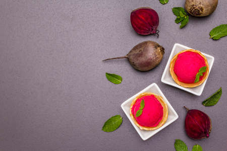 Beet ice cream, sorbet, gelato. Summer healthy refreshment dessert. Vegetarian (vegan) trendy food concept. With fresh vegetables and mint. Stone concrete background, copy space, top view