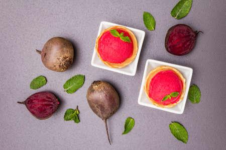 Beet ice cream, sorbet, gelato. Summer healthy refreshment dessert. Vegetarian (vegan) trendy food concept. With fresh vegetables and mint. Stone concrete background, top view