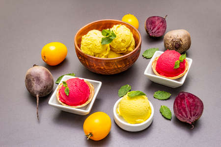 Assorted of beet and tomato ice cream, sorbet, gelato. Summer healthy refreshment dessert. Vegetarian (vegan) trendy food concept. With fresh vegetables and mint. Stone concrete background