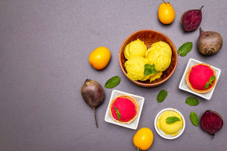 Assorted of beet and tomato ice cream, sorbet, gelato. Summer healthy refreshment dessert. Vegetarian (vegan) trendy food concept. Fresh vegetables, mint. Stone concrete background copy space top view