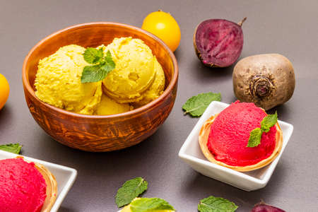 Assorted of beet and tomato ice cream, sorbet, gelato. Summer healthy refreshment dessert. Vegetarian (vegan) trendy food concept. With fresh vegetables and mint. Stone concrete background, close up