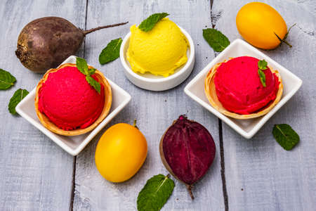 Assorted of beet and tomato ice cream, sorbet, gelato. Summer healthy refreshment dessert. Vegetarian (vegan) trendy food concept. With fresh vegetables and mint. Wooden boards background, close up Zdjęcie Seryjne