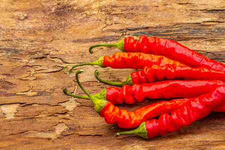 Red and orange chili pepper cooking food background. Traditional ingredients for preparation healthy vegan (vegetarian) meal. Wooden bark background, copy space, close up