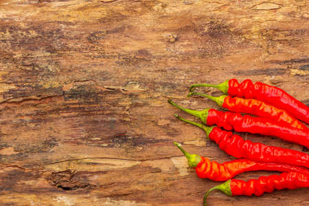 Red and orange chili pepper cooking food background. Traditional ingredients for preparation healthy vegan (vegetarian) meal. Wooden bark background, copy space, top view