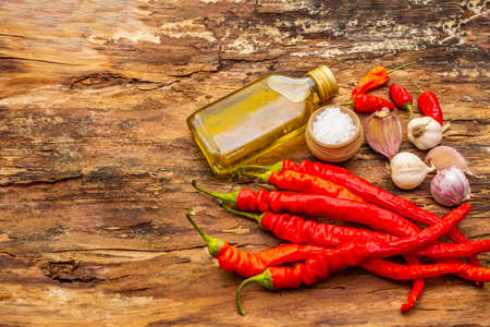 Red and orange chili pepper with garlic cooking food background. Traditional ingredients for preparation healthy meal. Sea salt, olive oil, wooden bark background, copy space Reklamní fotografie