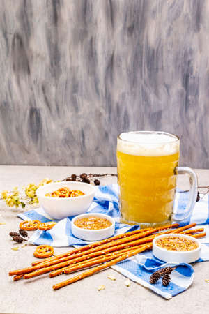 Oktoberfest set. Light beer, pretzels, mustard, sesame straw, hop. Traditional German cuisine, festival food. Bottles, linen napkin, stone concrete background, wooden backdrop copy space