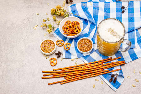 Oktoberfest set. Light beer, pretzels, mustard, sesame straw, hop. Traditional German cuisine, festival food. Bottles, linen napkin, stone concrete background, wooden backdrop copy space, top view