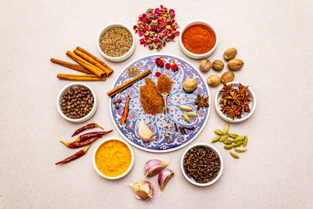 Ras el Hanout, exotic luxury spice. Ingredients for preparation oriental spice mix in ceramic bowls. An essential spice for any Moroccan dishes. Stone background, top view, copy space