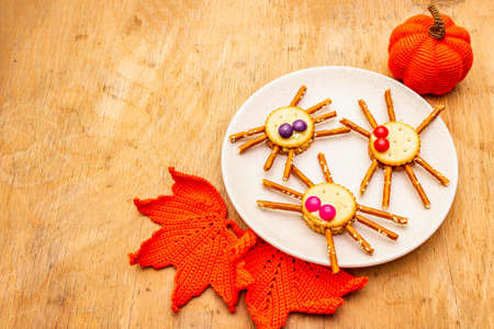 Funny kids food. Edible spiders from cookies, small candies and sweet sesame sticks. Halloween concept with autumn leaves, pumpkin. Ceramic plate, wooden background, copy space Standard-Bild