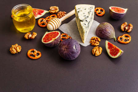 Cheese appetizer selection or wine snack set. Blue cheese, figs, honey, walnuts, pretzels. Traditional healthy antipasti on black stone concrete background, copy space