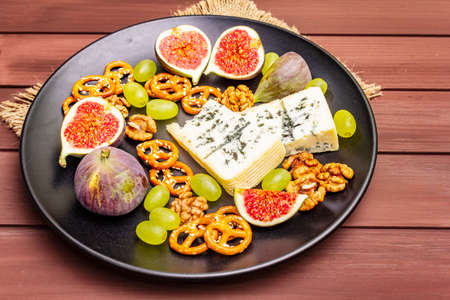 Cheese plate with blue cheese, honey, walnuts, figs, grapes, pretzels. Traditional healthy appetizer, snack, antipasti. Wooden boards background, vintage sackcloth, copy space, close up