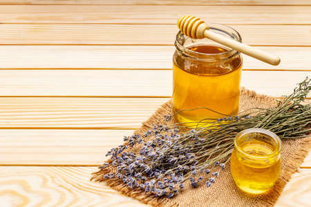 Fresh liquid honey in glass jars with a wooden honey dipper. Healthy sugars nutrition concept. Dry lavender bouquet, vintage sackcloth, wooden boards background, copy space Stok Fotoğraf