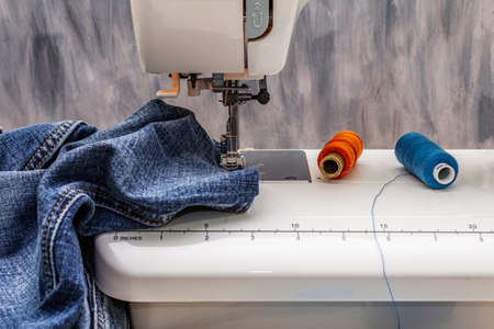 Sewing machine foot on denim. Scissors, spools of thread. Stands on a table, wooden backdrop