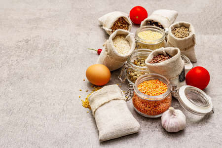Zero waste food shopping concept. Cereals, pasta, legumes, dried mushrooms, spices, fresh vegetables. Sustainable lifestyle, stone concrete background, copy space