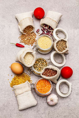 Zero waste food shopping concept. Cereals, pasta, legumes, dried mushrooms, spices, fresh vegetables. Sustainable lifestyle, stone concrete background, top view