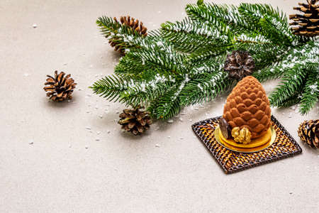 Festive dessert in the shape of a Christmas fir cone. New Year sweet treat concept. Stone concrete background, copy space
