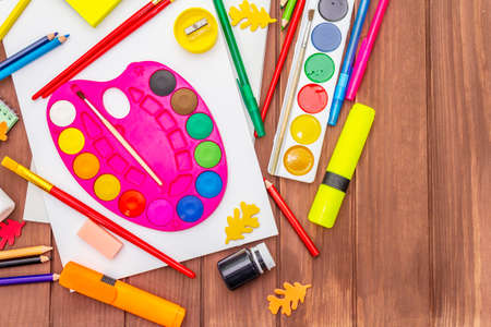 Back to school concept. School education supplies on brown wooden boards background, flat , top view