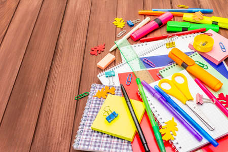 Back to school concept. School education supplies on brown wooden boards background, flat lay, copy space