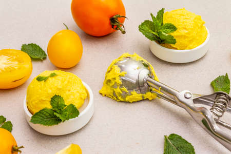 Yellow tomato ice cream, sorbet, gelato. Summer healthy refreshment dessert. Vegetarian (vegan) trendy food concept. With fresh vegetables and mint. Stone concrete background, close up