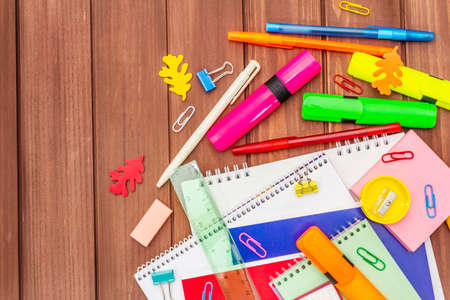 Back to school concept. School education supplies on brown wooden boards background, flat lay, copy space, top view