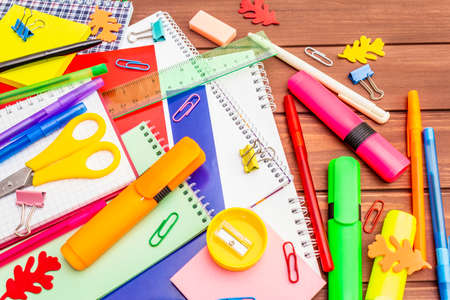 Back to school concept. School education supplies on brown wooden boards background, flat lay, close up