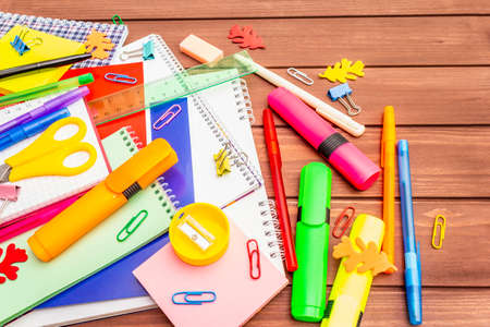 Back to school concept. School education supplies on brown wooden boards background, flat lay