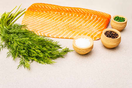 Cooking fresh raw salmon. Ingredients for marinated and salted fish. Preparation healthy seafood eating. Sea salt, pepper, dill. Light stone concrete background, copy space