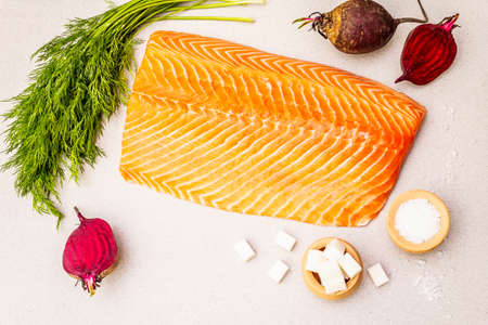 Gravlax, traditional scandinavian cooking salmon. Fresh raw ingredients for preparation healthy seafood eating. Spice, beet, sea salt, pepper, dill. Light stone concrete background, top view, close up