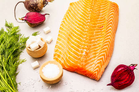 Gravlax, traditional scandinavian cooking salmon. Fresh raw ingredients for preparation healthy seafood eating. Spice, beet, sea salt, pepper, dill. Light stone concrete background, close up