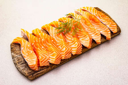 Slices of fresh salmon fish. Raw ingredient for cooking healthy seafood. Concept omega 3 containing food. Vintage wooden cutting board, stone concrete background, copy space